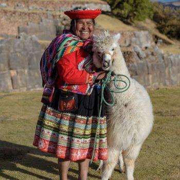Cuzco, Peru - July 14, 2018. Peruvian woman dressed in traditional colourful clothes with alpaca / llama at Sacsayhuaman, Cusco, Peru, South America.